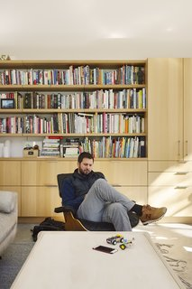 Space and Storage Needs Guide the Expansion of a Family's Cottage North of San Francisco - Photo 5 of 12 - Tim reclines in an Eames Lounge. The bookcase behind him connects to the kitchen storage system.