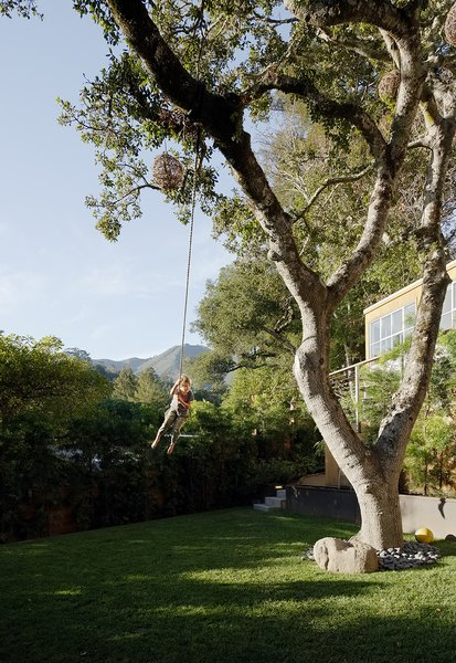 Leo flies across the yard on a rope swing (opposite). The oak's trunk is surrounded by Mexican river stones.