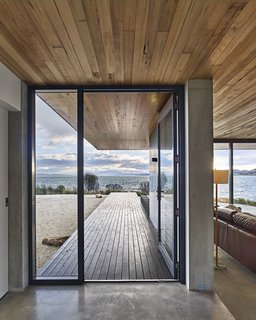 A Semi-Modular Beach House in Tasmania Floats Over a Site That Survived a Bushfire - Photo 1 of 9 - The dwelling's concrete slab meets a New Zealand pine deck at the custom steel entrance door. Styled by Julia Landgren