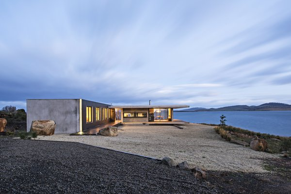 The Younger family vacation home is a semi-modular structure made of wood, steel, glass, and precast concrete. It's surrounded by Tasman gold gravel, which acts as  a buffer zone in case of a bushfire. A building-height LED light accentuates an exterior corner.