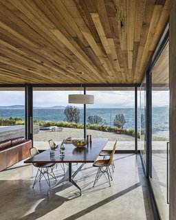 A Semi-Modular Beach House in Tasmania Floats Over a Site That Survived a Bushfire - Photo 4 of 9 - The dining table and chairs are by Charles and Ray Eames. The ceiling, which extends beyond the building's envelope, is made of Tasmanian oak. Styled by Julia Landgren