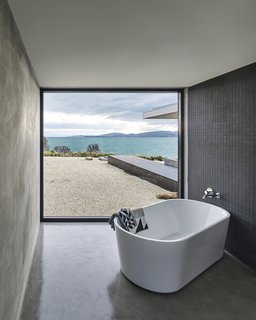 A Semi-Modular Beach House in Tasmania Floats Over a Site That Survived a Bushfire - Photo 5 of 9 - The corner bathroom is defined by a freestanding Kado Lure 1760 tub and a powerful view of the bay. Styled by Julia Landgren