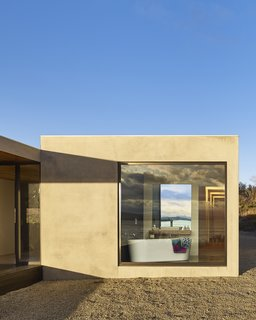 """A Semi-Modular Beach House in Tasmania Floats Over a Site That Survived a Bushfire - Photo 7 of 9 - The aluminium-framed windows throughout are by Australian company Capral.""""We wanted as<br>much glass as possible to enjoy the almost 360-degree views,"""" says resident Sarah Younger. Styled by Julia Landgren"""