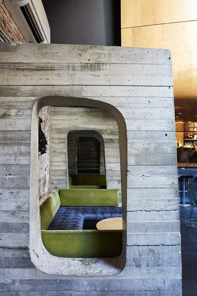 The first-floor auditorium/recording studio is located in a curvaceous wood pod that hovers above the bar in the basement. Concrete structural buttresses support the wall and act as stylized booth dividers.