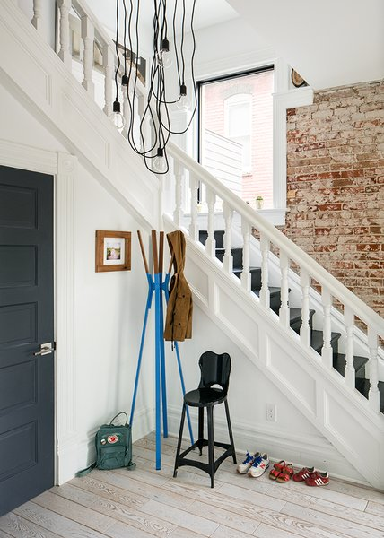 "Architect Caroline Wilding, then of Denver-based Design Platform, led the renovation. The staircase needed some treads replaced, but ""was left as original as possible,"" she says. Wilding created the chandelier using wires from Color Cord and brackets from Home Depot. - Denver, Colorado Dwell Magazine : September / October 2017"