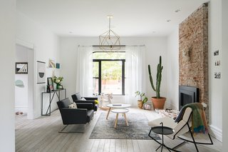 Putting Down Roots in Denver, Ballplayer Josh Thole Renovates a 19th-Century Victorian - Photo 9 of 12 - In the living room, layers of plaster were removed to expose the original brick fireplace surround, and a brick step was added; the black metal gas insert is by Heat & Glo. Tablo Tables from Normann Copenhagen sit on a rug from Safavieh, and the light fixture was designed and fabricated by Nathan Warner of Warbach.