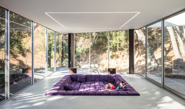The living room features a 250-square-foot configuration of Patricia Urquiola's Tufty-Time sofa for B&B Italia. Overhead, as in the rest of the main living spaces, flush- mounted LED strips provide further demarcation of zones.