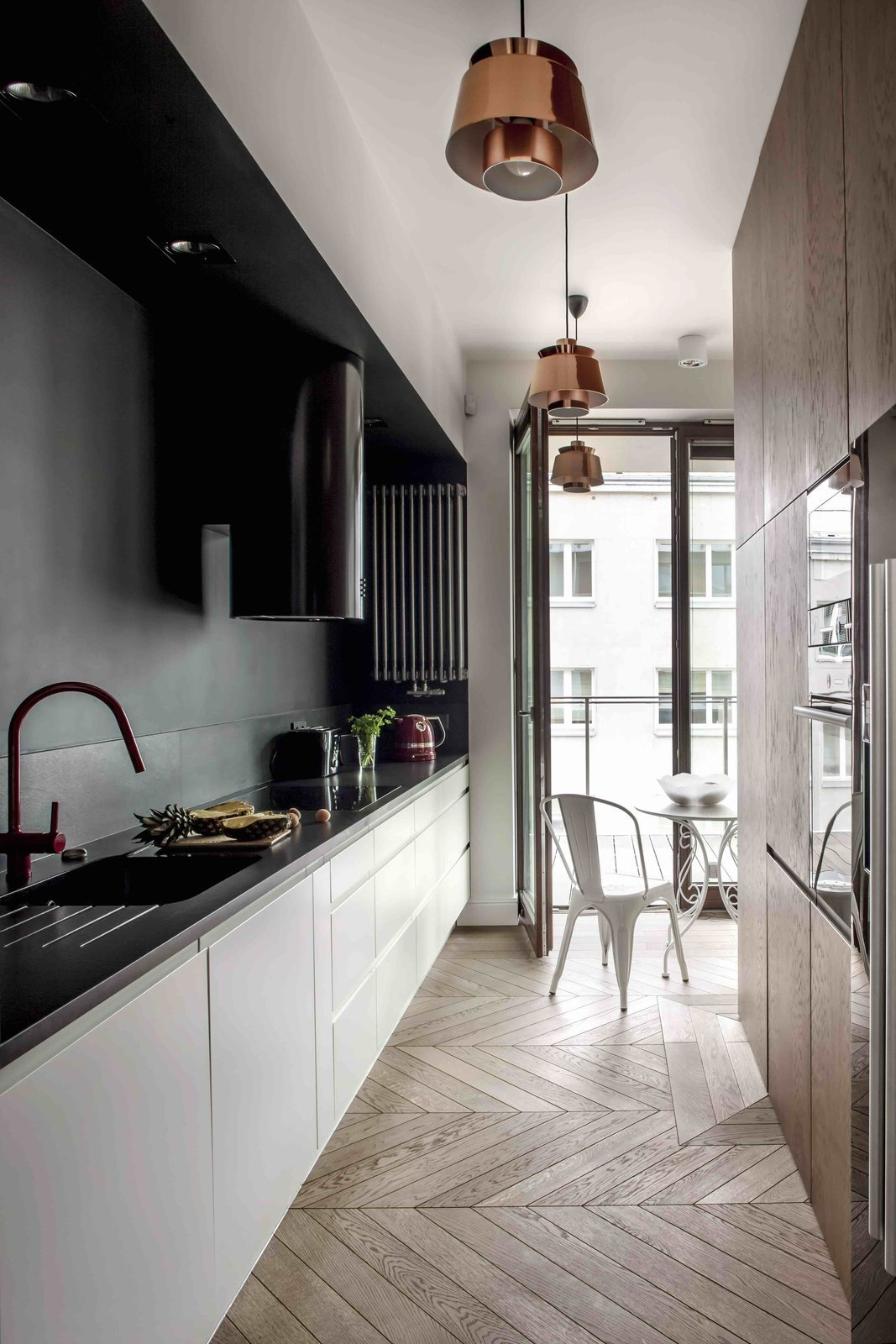 Tagged: Kitchen, Wood, White, Light Hardwood, Pendant, Recessed, Drop In, Range Hood, and Range.  Best Kitchen Light Hardwood Drop In Photos from Filled With Color and Pattern, This Eclectic Apartment Brings a Little Madrid to Warsaw