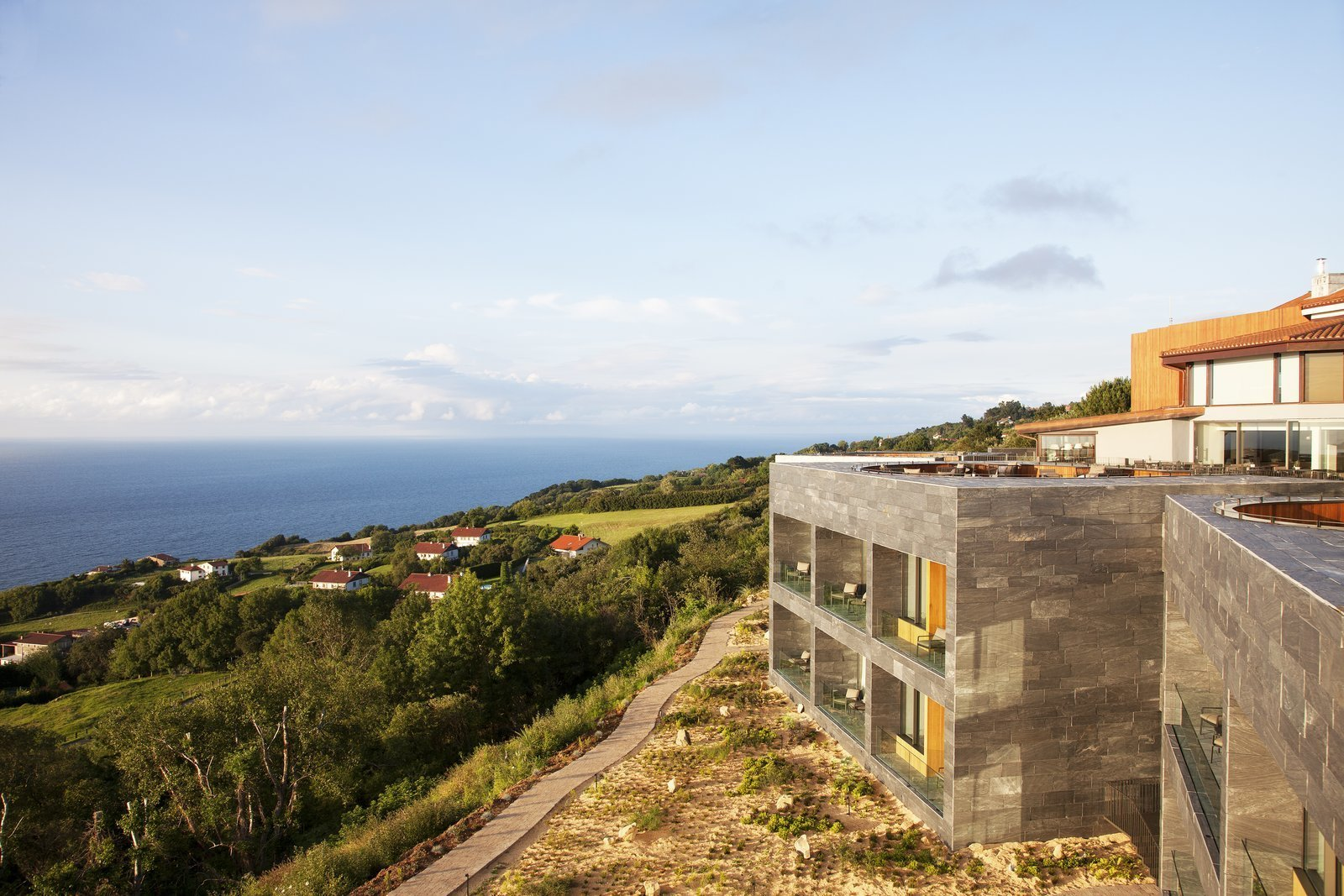 Comprised of five stone cubicles that are built into the hillside facing the sea, the structure features a rooftop deck with slightly sunken outdoor pits for guests to enjoy. The terraces are connected by a series of planked decking and landscaped gardens that offer a spectacular panoramic view of the coastline.