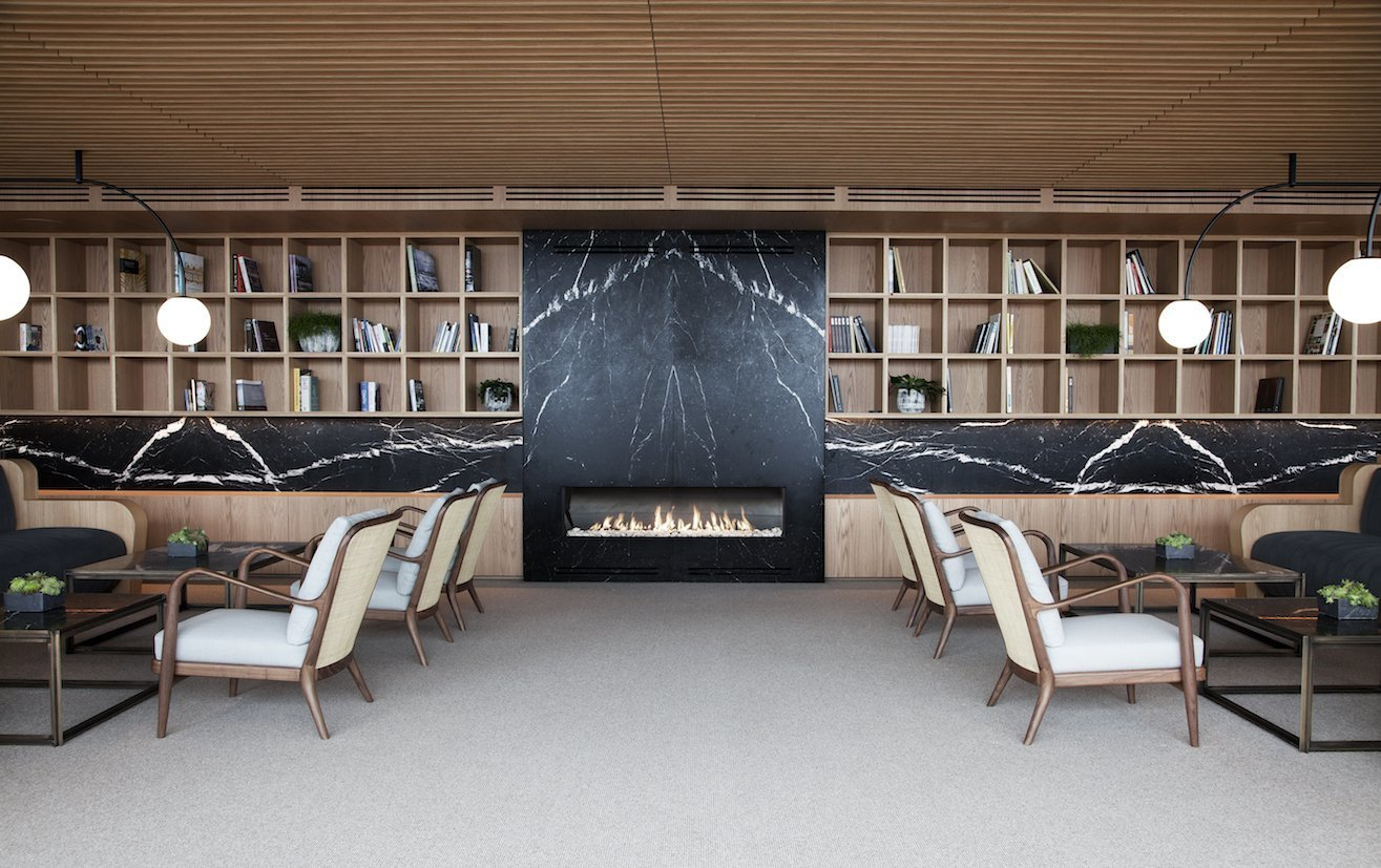 The hotel's interiors emphasizes the use of natural materials such as stone, wood, and linen.  The hotel's interiors are equally notable for their elegant and contemporary decor that emphasizes the use of natural materials.  The common areas are paneled in wood—a theme that runs throughout the public spaces—seamlessly interconnecting them. The minimalist guest rooms also feature warm wood paneling and floor-to-ceiling windows and terraces. Interiors are furnished with pieces from Spanish furniture maker Kettal, including the collaborative collections Bitta and Boma by Rodolfo Dordoni, Park Life by Jasper Morrison, and Cala by Doshi Levien.
