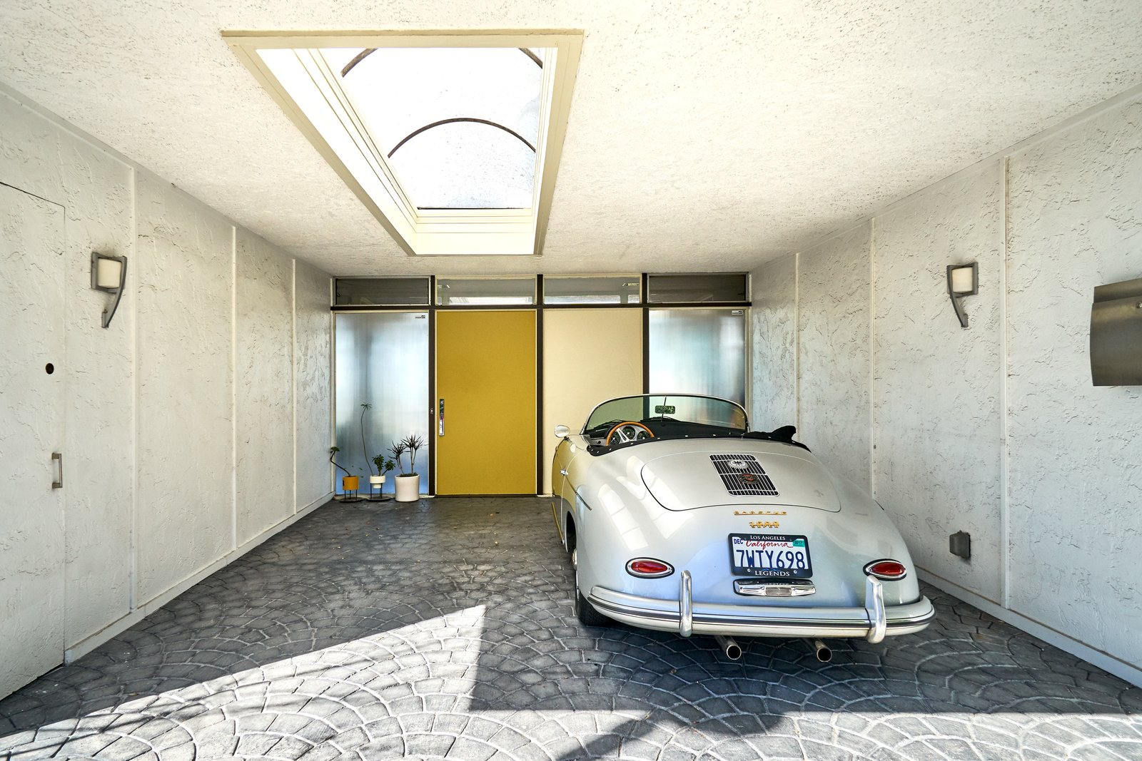 Entry through the skylit carport gives way to the classic mid-century yellow door, complete with original hardware. Tagged: Garage.  Photo 14 of 14 in A Midcentury-Modern Home in L.A. Designed by Richard Banta Is For Sale For $899K