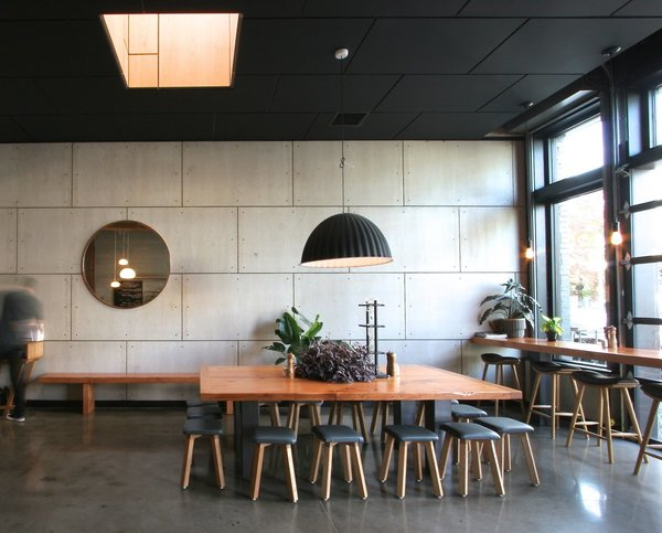 Large, communal tables, sound absorbing ceiling tiles, and street-side seating impart a cozy feel.