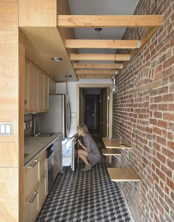 This Compact Apartment in NYC Is Full of Crafty Solutions - Photo 5 of 18 - Original wood beams and the brick wall are the surviving hallmarks of the previous apartment. The space now contains three bedrooms instead of the original two. The brick wall is the spine of the apartment; all rooms radiate from it.
