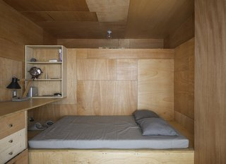 This Compact Apartment in NYC Is Full of Crafty Solutions - Photo 7 of 18 - Peter conceived a stepped program for the layout. Placing the rooms at different levels created cavities for storage as well as for furnishings, such as the dining table and benches and the bed in Olia's studio, which when not in use slide into the space beneath the raised floor in Peter's office, above.