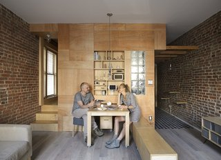 This Compact Apartment in NYC Is Full of Crafty Solutions - Photo 2 of 18 - Peter and his wife, artist Olia Feshina, relax inside their apartment in New York's Washington Heights.