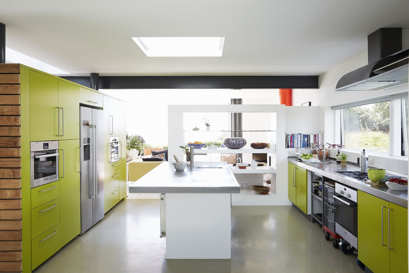 Equipped with Bosch appliances and a 16-foot steel countertop, the kitchen was tailor-made by architect and resident Nick Evans for his wife, Celia Sellschop, a chef.  Pett Level, England Dwell Magazine : November / December 2017 Tagged: Kitchen, Refrigerator, Wall Oven, Range, Microwave, Drop In, Metal, and Colorful.  Best Kitchen Refrigerator Wall Oven Microwave Photos from Fall in Love With This British Architect's Colorful Weekend Retreat
