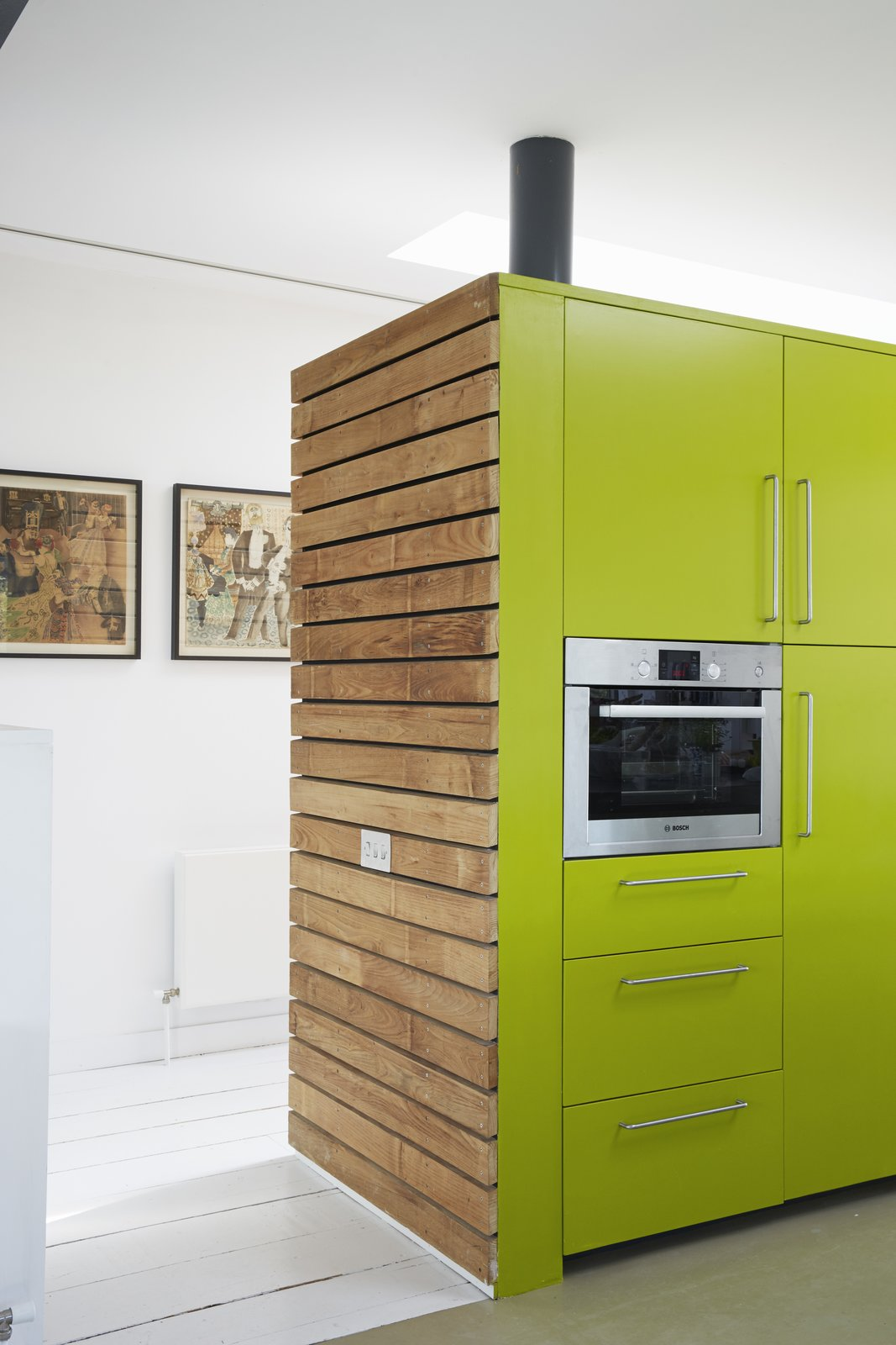 The sides of the cabinets are clad in sweet chestnut; their faces are painted a custom shade of green by Dulux.  Pett Level, England Dwell Magazine : November / December 2017 Tagged: Kitchen, Colorful Cabinet, Painted Wood Floor, and Wall Oven.  Photo 5 of 14 in Fall in Love With This British Architect's Colorful Weekend Retreat