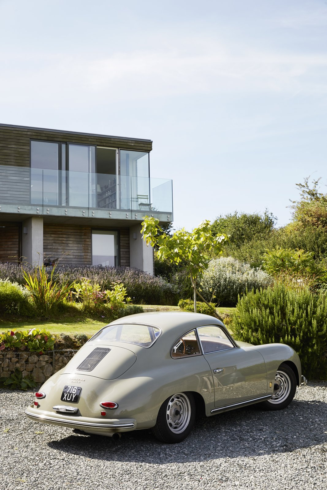 Nick's passion for midcentury design extends to cars. His 1959 Porsche 356A coupe is parked in the driveway.  Pett Level, England Dwell Magazine : November / December 2017 Tagged: Outdoor, Grass, Shrubs, Stone Patio, Porch, Deck, and Front Yard.  Photo 7 of 14 in Fall in Love With This British Architect's Colorful Weekend Retreat