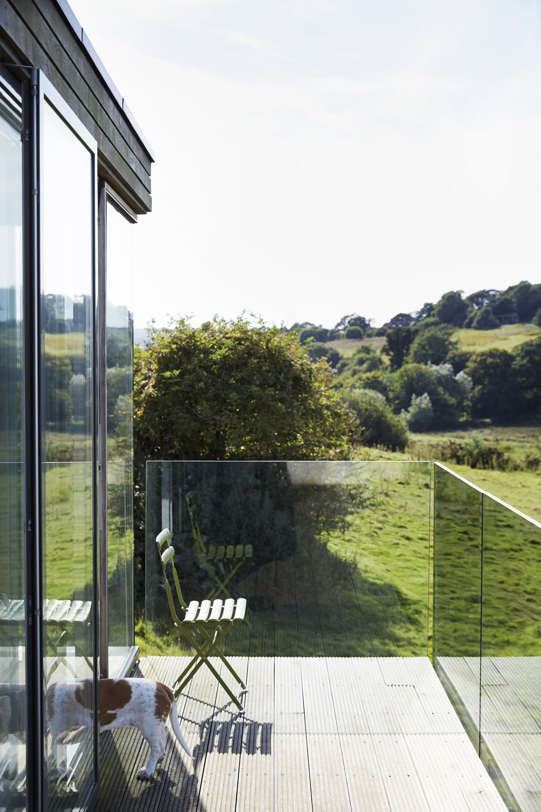 For uninterrupted views, the balcony is wrapped in glass panels.  Pett Level, England Dwell Magazine : November / December 2017 Tagged: Outdoor and Wood Patio, Porch, Deck.  outside by Molly E. Osler, Interior Design from Fall in Love With This British Architect's Colorful Weekend Retreat