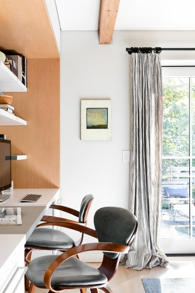 Beside the kitchen, two Cherner armchairs are paired with a built-in desk that extends from the cabinets, made by Corsi.