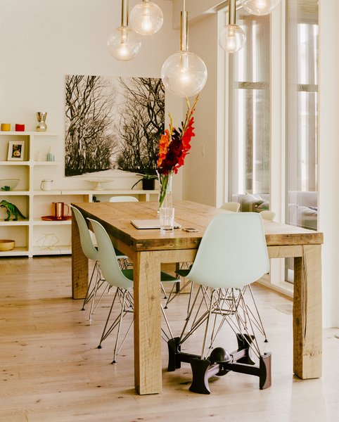 One of the Eames Molded Plastic chairs is lifted on a Kaboost base so that a child can eat at the dining table  East St. Paul, Manitoba Dwell Magazine : November / December 2017