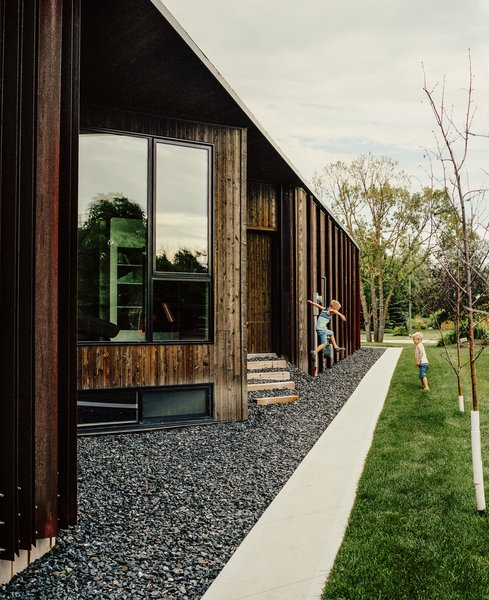 Beyond a bed of black granite rocks, an entrance is concealed in an alcove in the home's cedar-and-weathered-steel facade. The windows were manufactured by Duxton Windows & Doors.