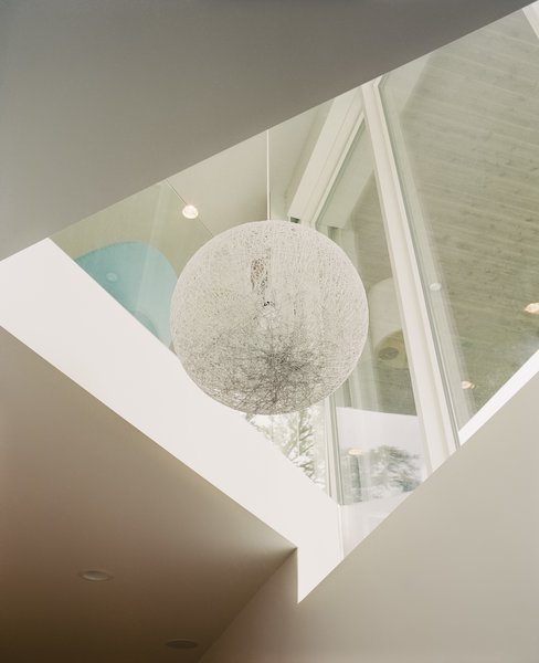 A Tahsis pendant by EQ3 hangs in a triangular shaft above the basement, which is built-out to provide extra space for the single-story house.