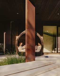 The Parallelogram House Helps Reshape a Sleepy Canadian City - Photo 10 of 11 - Rachel reclines in a daybed on the patio outside the master bedroom.