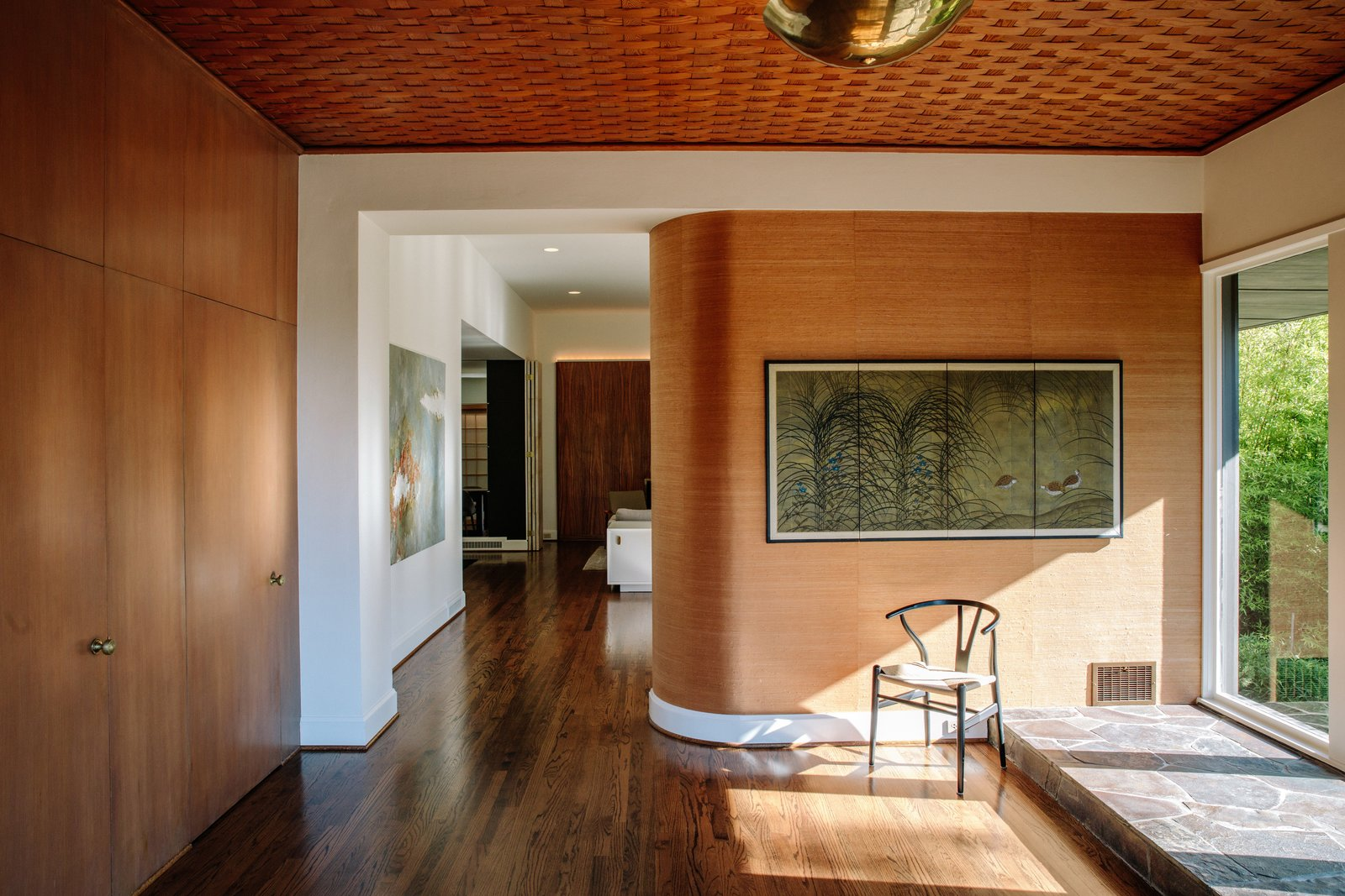 A curved zebrawood wall greets visitors in the foyer. Tagged: Living Room, Chair, Medium Hardwood Floor, and Ceiling Lighting.  Photo 3 of 15 in Nearly 80 Years Later, an Architect Rescues a Japanese-Inspired  Masterwork Designed by His Father
