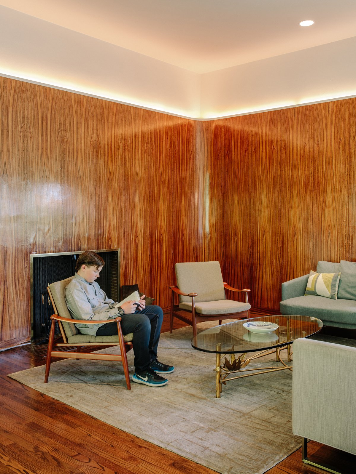 In the hearth, more zebrawood paneling is accented by LED strips. Tagged: Living Room, Medium Hardwood Floor, Recessed Lighting, Rug Floor, Chair, Standard Layout Fireplace, Sofa, and Coffee Tables.  Photo 5 of 15 in Nearly 80 Years Later, an Architect Rescues a Japanese-Inspired  Masterwork Designed by His Father
