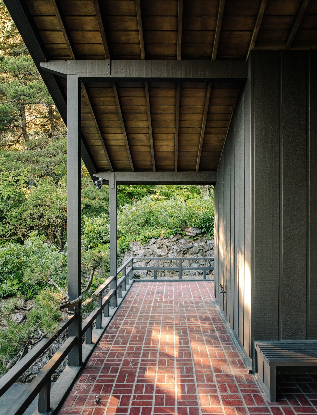 The 2,300-square-foot home's overhangs shelter its porches. Tagged: Outdoor, Pavers Patio, Porch, Deck, Stone Patio, Porch, Deck, Trees, Boulders, and Shrubs.  Photo 10 of 15 in Nearly 80 Years Later, an Architect Rescues a Japanese-Inspired  Masterwork Designed by His Father