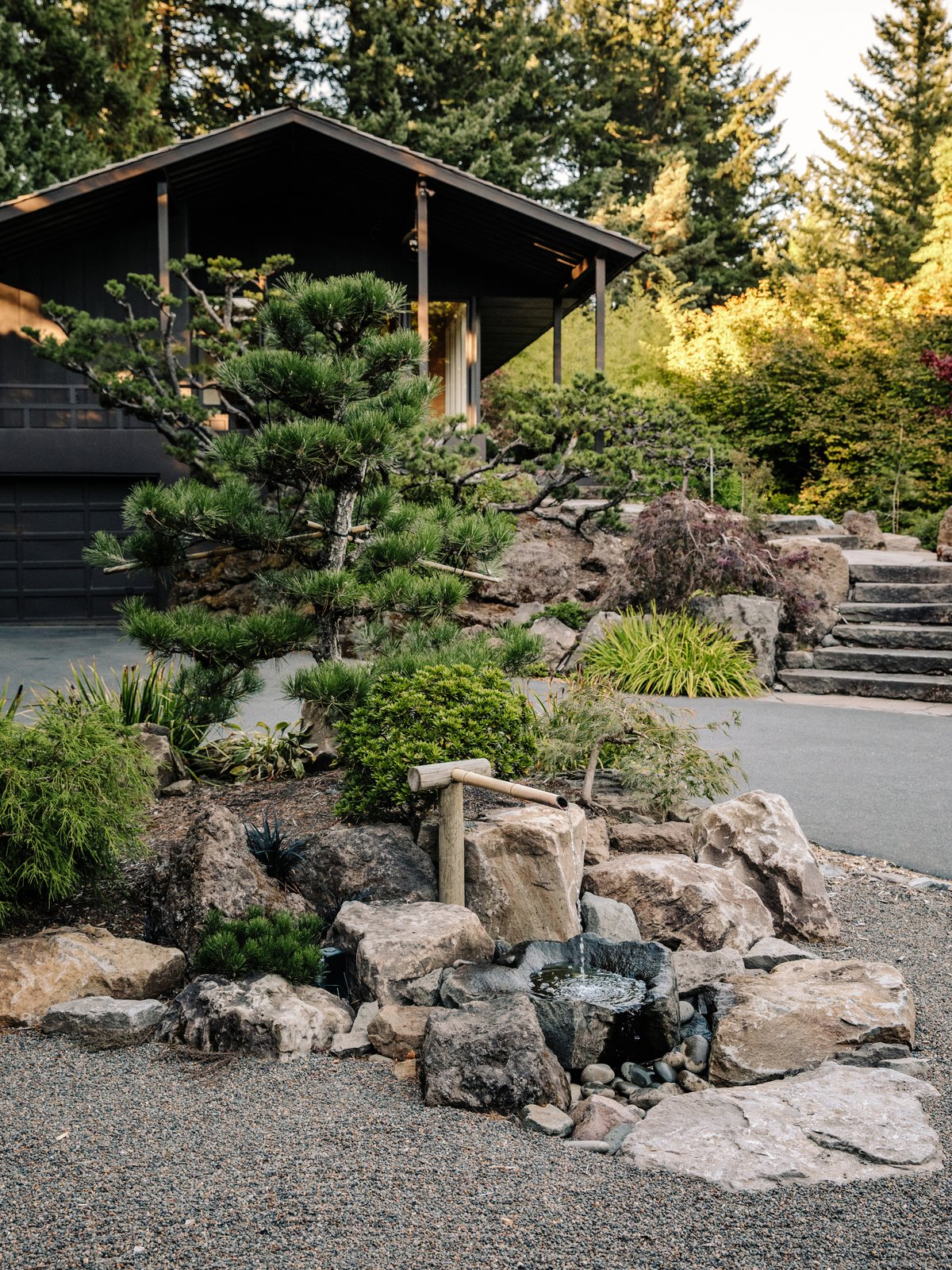 A Japanese-style Bamboo water fountain sits in the driveway. Tagged: Outdoor, Boulders, Trees, Front Yard, Walkways, Hardscapes, and Garden.  Photo 11 of 15 in Nearly 80 Years Later, an Architect Rescues a Japanese-Inspired  Masterwork Designed by His Father