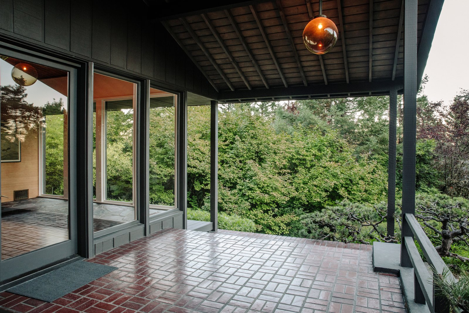 The front porch, clad with floor-to-ceiling glass windows, illuminates the foyer inside. Tagged: Outdoor, Trees, and Pavers Patio, Porch, Deck.  Photo 13 of 15 in Nearly 80 Years Later, an Architect Rescues a Japanese-Inspired  Masterwork Designed by His Father