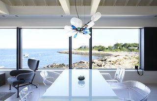 On the Coast of Massachusetts, a Prefab Ranch Is Totally Overhauled for a Wheelchair-User - Photo 6 of 11 - Expanded windows open the first floor to sweeping views of Gap Cove. An assortment of molded acrylic chairs joins a Parsons table from Room & Board.