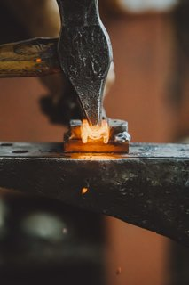 Meet a Seasoned Blacksmith Who Reveals His Art's Painstaking Process - Photo 5 of 13 - Shaping the Handle: With the piece steadied in a cradle, Howard creases the back of the bar with the peen of his hammer, in effect distorting the metal so that it's not so rectilinear This is one of the design's few aesthetic flourishes.