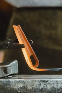 Meet a Seasoned Blacksmith Who Reveals His Art's Painstaking Process - Photo 7 of 13 - Wrapping the Handle: Around the tear-shaped loop of the handle, Howard drapes the heated, now-triangular piece, fusing it to the handle to give it more dimension. Howard likens this to adding moulding to a room.