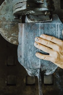 Meet a Seasoned Blacksmith Who Reveals His Art's Painstaking Process - Photo 10 of 13 - Sizing the Blade: With his hand on the flattened blade, Howard measures and marks the excess material of the now-cold metal so he can cut it with a shear, which is mounted onto his work table.