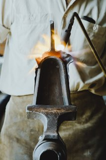 """Meet a Seasoned Blacksmith Who Reveals His Art's Painstaking Process - Photo 11 of 13 - Shaping the Blade: A special anvil called a """"stake"""" is held in a T-shaped vice. With a torch in his left hand and a hammer in his right, Howard shapes the blade of the shovel around the bell-shaped stake."""
