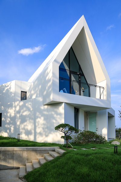 Clad in a white Hi-Macs acrylic surface, a house belonging to two painters in Sokcho, South Korea, is intended as a blank canvas that captures light and shadow. - Sokcho, South Korea Dwell Magazine : November / December 2017