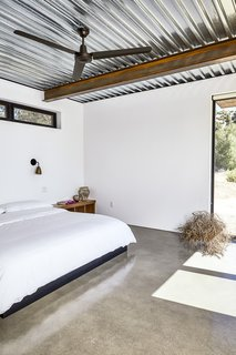 At This High-Desert Home, a Whole Wall Opens Up When You Crank a Giant Wheel - Photo 7 of 10 - The master bedroom occupies one of three units extending off the main space. Like other furnishings, the bed was made by steel fabricators.