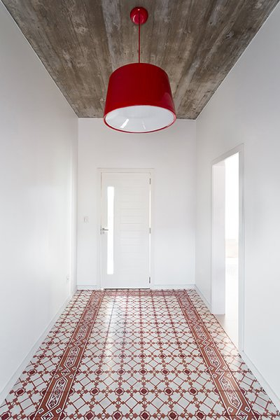 A red Cloche pendant by Newline complements the Fabrica de Mosaicos tile in the entryway. - Pato Branco, Brazil Dwell Magazine : November / December 2017