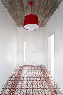 A Brazilian Architect Builds a Dream Home For Her Parents - Photo 3 of 5 - A red Cloche pendant by Newline complements the Fabrica de Mosaicos tile in the entryway.