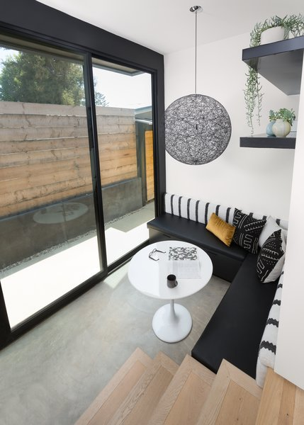 In the breakfast nook, an Ikea table is surrounded by a bench made specifically for the corner by CJS Custom Woodworking & Design. A Moooi pendant light and custom concrete floors distinguish the area.