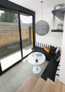 The Woman Who Grew Up in This L.A. Home Returned to Give it a Stunning Renovation - Photo 7 of 11 - In the breakfast nook, an Ikea table is surrounded by a bench made specifically for the corner by CJS Custom Woodworking & Design. A Moooi pendant light and custom concrete floors distinguish the area.