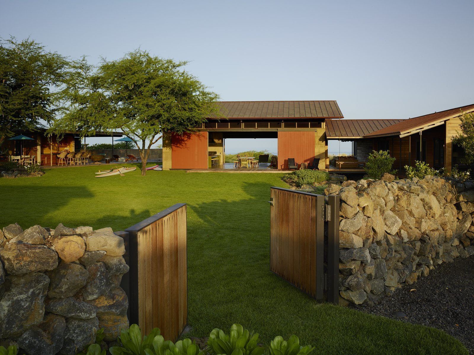 Tagged: Outdoor, Front Yard, Trees, Grass, Shrubs, Wood Fences, Wall, and Walkways.  Photo 1 of 20 in An Incredible Home in Hawaii That's As Much Fun As Summer Camp