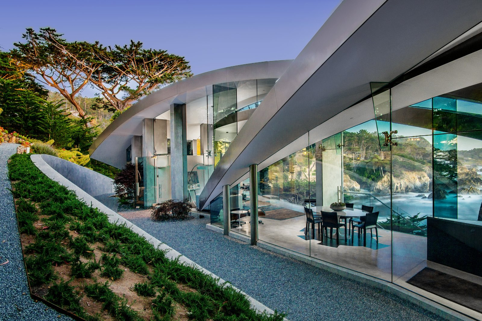 Tagged: Exterior, Curved RoofLine, Metal Roof Material, Glass Siding Material, House, and Beach House Building Type.  Best Photos from We Wish We Had $11.4M to Buy This Oceanfront Wonder in Carmel