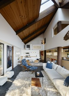 You'd Never Guess This Japanese-Style Home in Tiburon Is a Kit House - Photo 3 of 12 - Openings in the ceiling allow sunlight to wash over the black slate floors and fir columns. A velvet-upholstered Mr. Chair by George Mulhauser adds color to the living room.