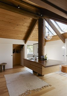 You'd Never Guess This Japanese-Style Home in Tiburon Is a Kit House - Photo 7 of 12 - For the heart of the space, Hale designed a double vanity—fabricated with wood from the original house—around an existing column. The pendant is by Lindsey Adelman.