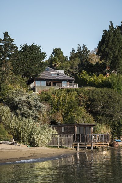 The property, situated on a steep bluff overlooking the San Francisco Bay, includes a main house with a deck, a pool, an outdoor kitchen, and a boathouse.