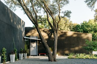 """A Black Stucco Home in Dallas Is Surrounded by Eye-Popping Greenery - Photo 1 of 17 - On a site adjacent to a greenbelt, architects Yen Ong and Paul Merrill of 5G Studio envisioned """"a solid black mass within an enclosed garden,"""" says Ong. A geothermal heat pump, solar panels, and rainwater harvesting helped the project achieve LEED Platinum status."""